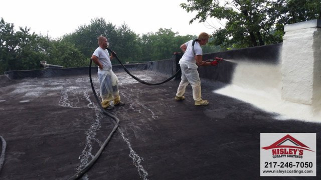 two roofing contractors applying our commercial roofing systems to a commercial roof